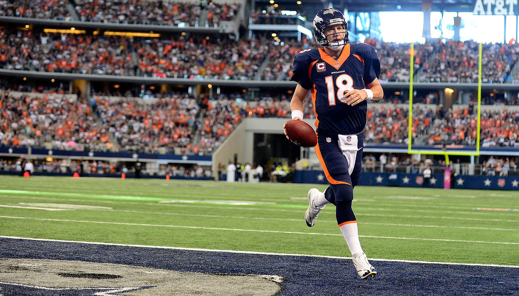 . Peyton Manning (18) of the Denver Broncos rushes for a touchdown untouched by the Dallas Cowboys defense during the first half. (Photo by AAron Ontiveroz/The Denver Post)