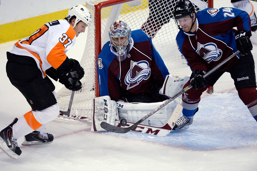 . Colorado Avalanche right wing Marc-Andre Cliche (24) pokes the puck out as Philadelphia Flyers left wing Jay Rosehill (37) and Colorado Avalanche goalie Semyon Varlamov (1) look on during the second period January 2, 2014 at Pepsi Center. (Photo by John Leyba/The Denver Post)