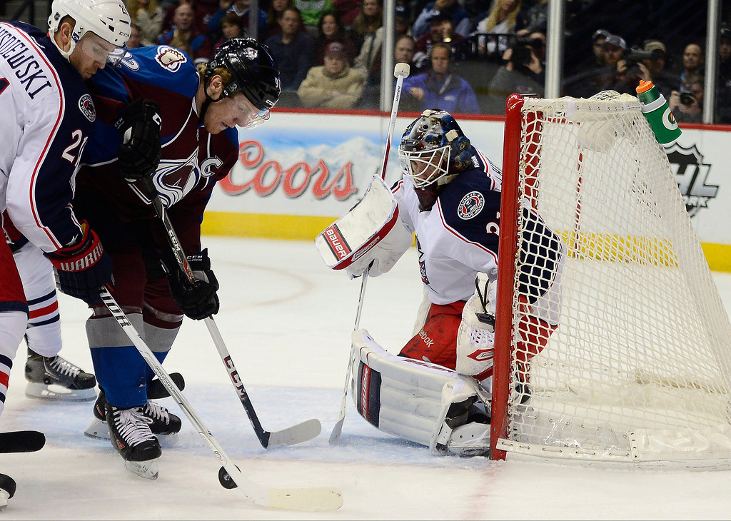 . Gabriel Landeskog (92) of the Colorado Avalanche and James Wisniewski (21) of the Columbus Blue Jackets vie for position as Curtis McElhinney (31) tends the net during the first period. The Colorado Avalanche hosted the Columbus Blue Jackets at the Pepsi Center on Tuesday, December 31, 2013. (Photo by AAron Ontiveroz/The Denver Post)
