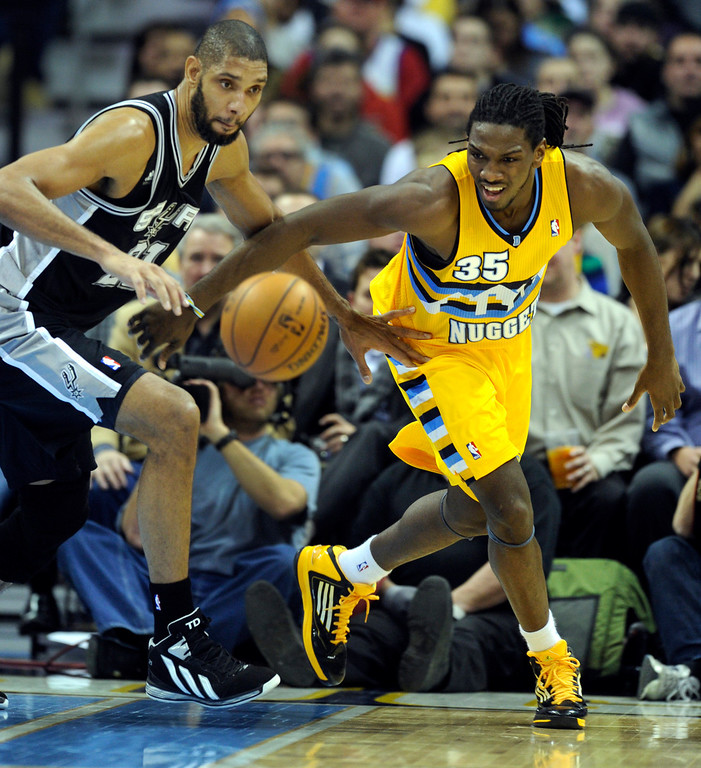 . Denver forward Kenneth Faried (35) contested a loose ball with Spurs forward Tim Duncan (21) in the first half. The Denver Nuggets hosted the San Antonio Spurs at the Pepsi Center Tuesday night, December 18, 2012. Karl Gehring/The Denver Post