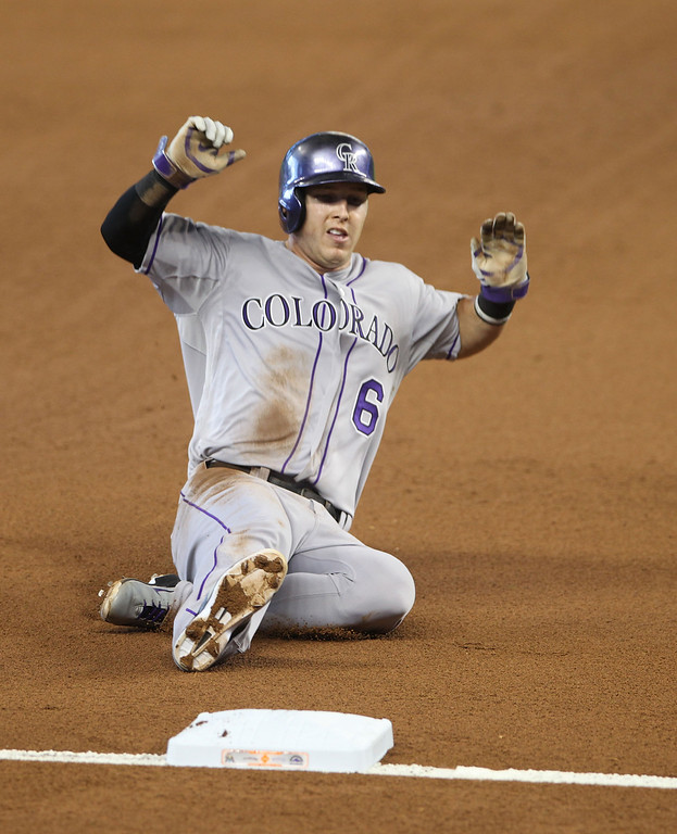 . Corey Dickerson #6 of the Colorado Rockies slides safely into third base during the second inning against the Miami Marlins at Marlins Park on April 3, 2014 in Miami, Florida.  (Photo by Marc Serota/Getty Images)