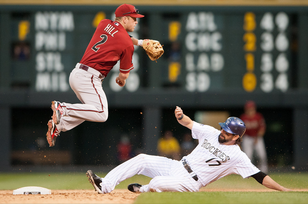 . Aaron Hill #2 of the Arizona Diamondbacks leaps on a double play attempt after forcing out the sliding Todd Helton #17 of the Colorado Rockies in the ninth inning of a game at Coors Field on September 22, 2013 in Denver, Colorado. The play resulted in only one out.  (Photo by Dustin Bradford/Getty Images)
