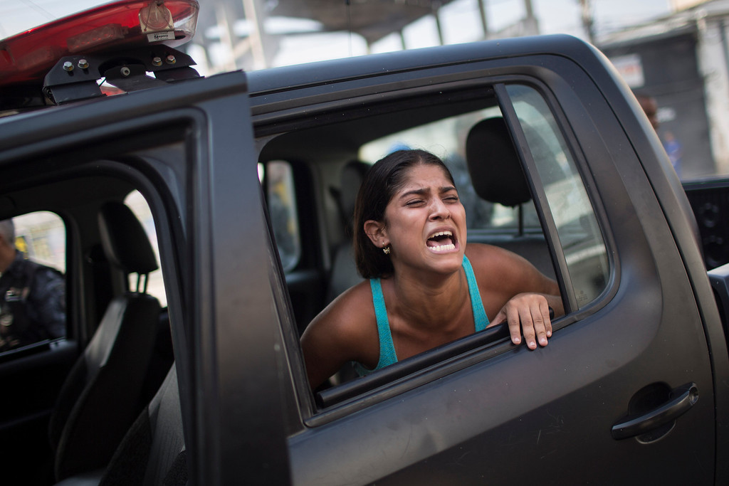 . A woman screams after being detained during protests near the area recently occupied by squatters in Rio de Janeiro, Brazil, Friday, April 11, 2014. The woman was later released. Squatters in Rio de Janeiro are clashing with police after a Brazilian court ordered that 5,000 people be evicted from abandoned buildings of a telecommunications company. Officers have used tear gas and stun grenades to try to disperse the families. (AP Photo/Felipe Dana)