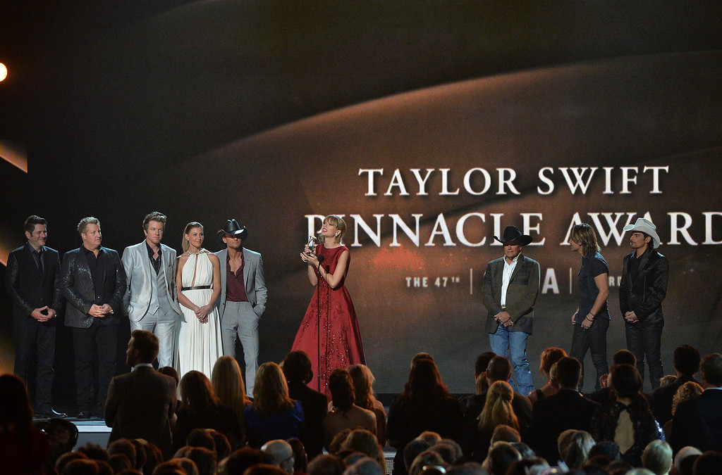 . NASHVILLE, TN - NOVEMBER 06:  Taylor Swift accepts The CMA Pinnacle Award onstage, presented by Jay DeMarcus, Joe Don Rooney and Gary LeVox of Rascall Flatts, Faith Hill, Tim McGraw, George Strait, Keith Urban and Brad Paisley during the 47th annual CMA Awards at the Bridgestone Arena on November 6, 2013 in Nashville, Tennessee.  (Photo by Rick Diamond/Getty Images)