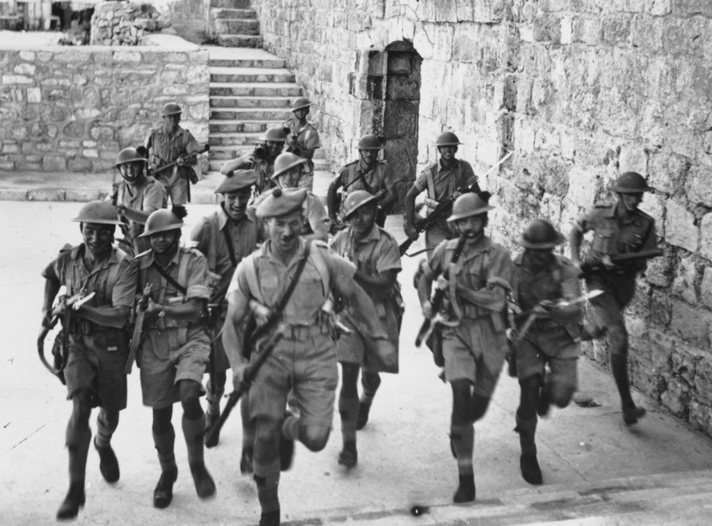 . British soldiers running through the old city of Jerusalem.   (Photo by Fox Photos/Getty Images)