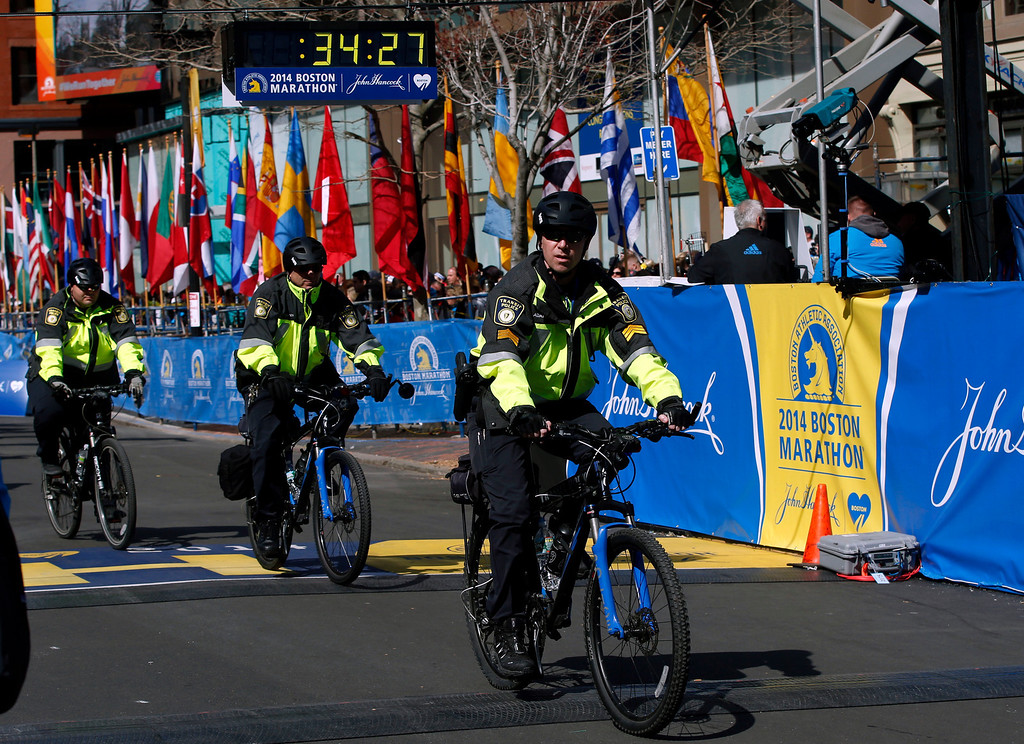 . Boston Police officers on bicycles ride across the finish line before during 118th Boston Marathon Monday, April 21, 2014 in Boston. (AP Photo/Elise Amendola)