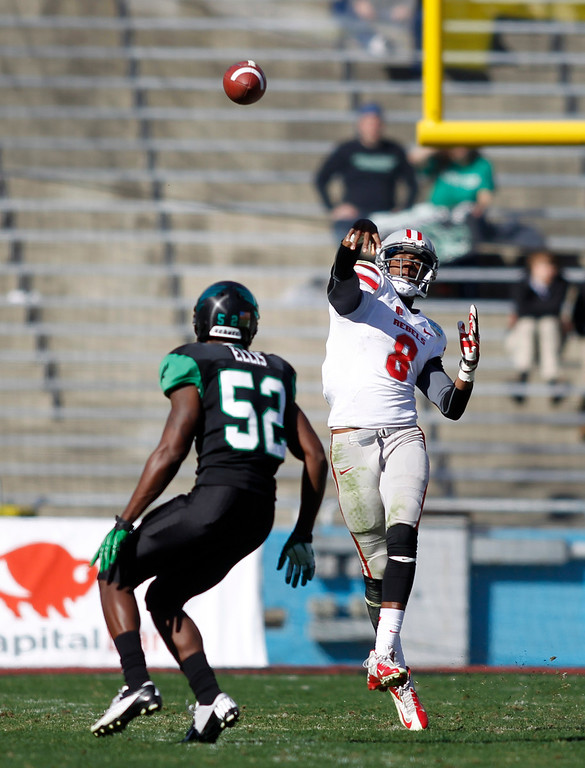 . UNLV quarterback Caleb Herring (8) unleashes a pass as North Texas linebacker Sed Ellis (52) contains during the first half of the Heart of Dallas NCAA college football game, Wednesday, Jan. 1, 2014, in Dallas. (AP Photo/Mike Stone)