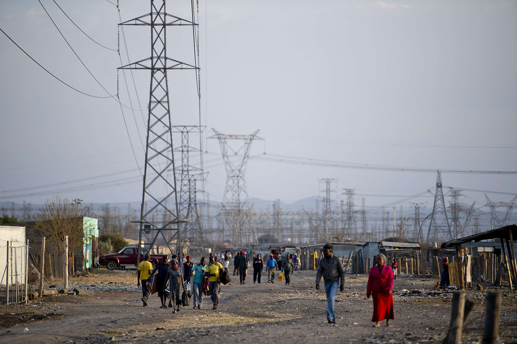 . People walk on July 9, 2013 in the Nkaneng shantytown next to the platinum mine, run by British company Lonmin, in Marikana. On August 16, 2012, police at the Marikana mine open fire on striking workers, killing 34 and injuring 78, during a strike was for better wages and living conditions. Miners still live in dire conditions despite a small wage increase.  ODD ANDERSEN/AFP/Getty Images