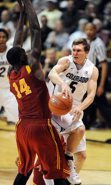 . Eli Stalzer of CU, passes around DeWayne Dedmon of USC during the second half of the January 10, 2013 game in Boulder.   Cliff Grassmick/Daily Camera