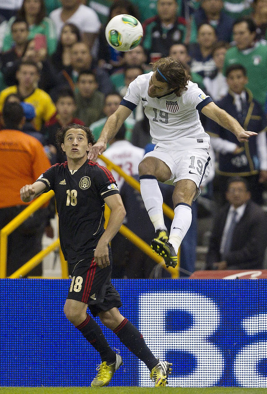 . United States\'  Zusi Graham, right,  heads for the ball with Mexico\'s Andres Guardado during a World Cup 2014 qualifying match at the Aztec stadium in Mexico City, Tuesday, March 26, 2013. (AP Photo/Christian Palma)