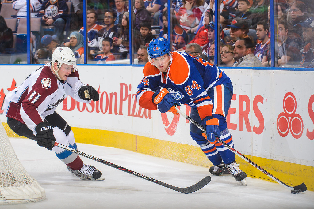 . Oscar Klefbom #84 of the Edmonton Oilers battles for the puck against Jamie McGinn #11 of the Colorado Avalanche during an NHL game at Rexall Place on April 8, 2014 in Edmonton, Alberta, Canada. The Avalanche defeated the Oilers 4-1. (Photo by Derek Leung/Getty Images)