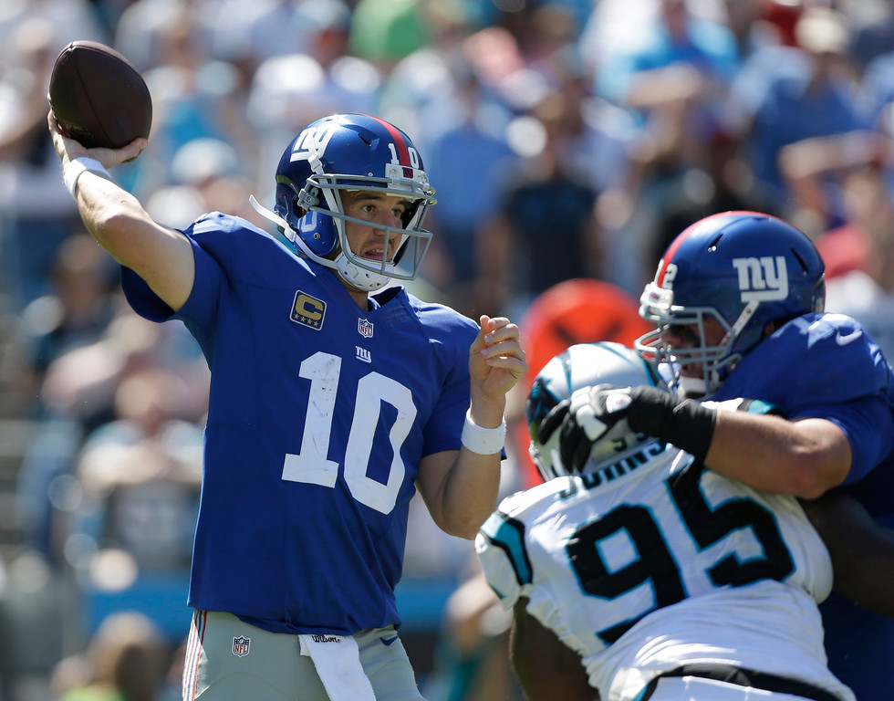 . New York Giants quarterback Eli Manning (10) looks to pass under pressure from Carolina Panthers\' Charles Johnson (95) during the first half of an NFL football game in Charlotte, N.C., Sunday, Sept. 22, 2013. (AP Photo/Bob Leverone)