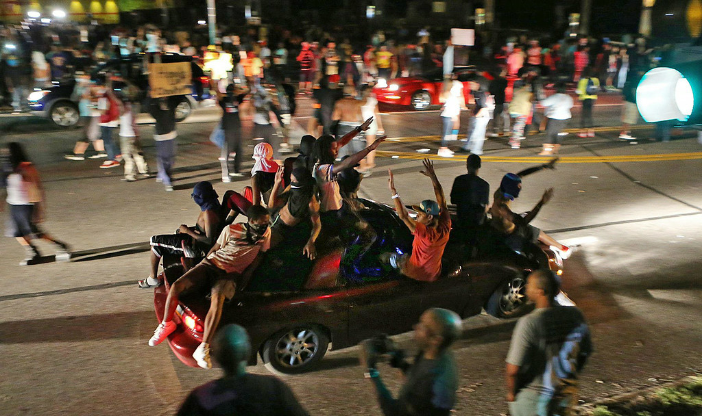 . Many people drove down the street honking their horns, raising their arms, and holding signs on W. Florissant in Ferguson on Thursday evening, Aug. 14, 2014, as some demonstrators stood in the middle of the street.  (AP Photo/St. Louis Post-Dispatch, J.B. Forbes)