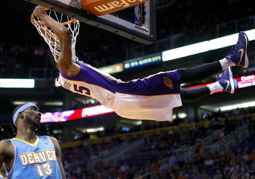 . Phoenix Suns\' Marcus Morris holds onto the rim after dunking as Denver Nuggets\' Corey Brewer looks away during the second half of an NBA basketball game, Monday, March 11, 2013, in Phoenix. (AP Photo/Matt York)