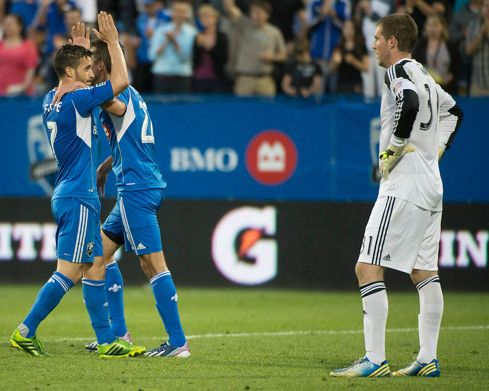 . Montreal Impact\'s Felipe Martins and Davy Arnaud celebrate a goal by Daniele Paponi as Colorado Rapids goalie Clint Irwin stands nearby during the second half of an MLS soccer game in Montreal on Saturday, June 29, 2013. (AP Photo/The Canadian Press, Peter McCabe)