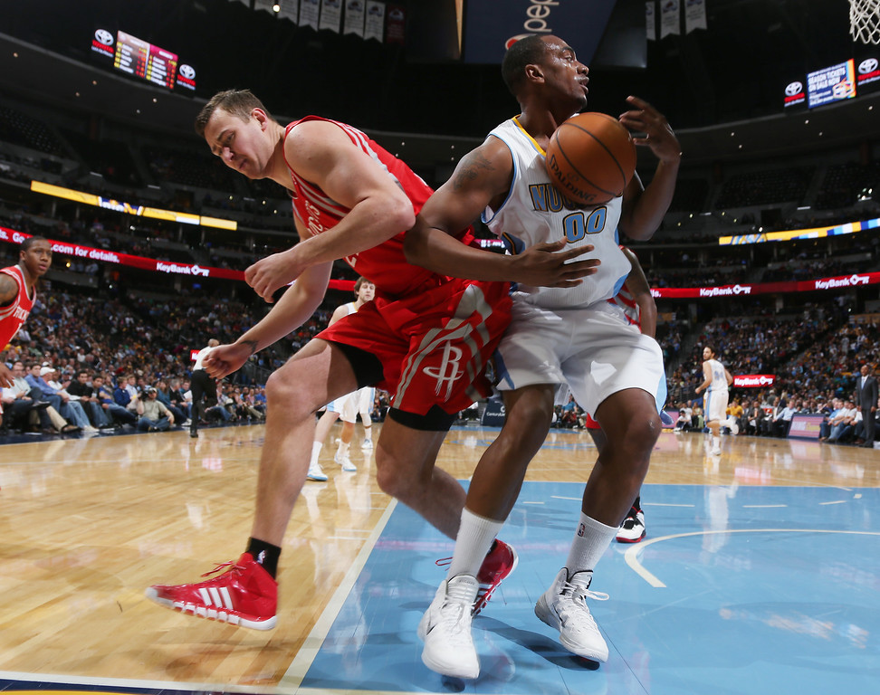 . Houston Rockets forward Donatas Motiejunas, left, of Lithuania, gets tangled up with Denver Nuggets forward Darrell Arthur as they fight for control of a loose ball in the fourth quarter of the Nuggets\' 123-116 victory in an NBA basketball game in Denver on Wednesday, April 9, 2014. (AP Photo/David Zalubowski)