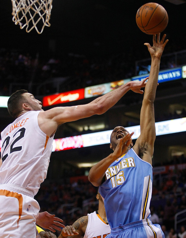 . Denver Nuggets small forward Anthony Randolph (15), right, shoots over Phoenix Suns center Miles Plumlee (22) in the second quarter during an NBA basketball game on Friday, Nov. 8, 2013, in Phoenix. (AP Photo/Rick Scuteri)