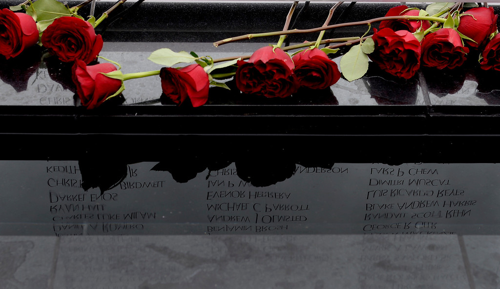 . Roses were placed at the wall with a reflection of the names on the wall. The memorial is a 21 glass panel and bears the names of nearly 6,000 Coloradans killed or MIA in all wars. (Photo By John Leyba/The Denver Post)