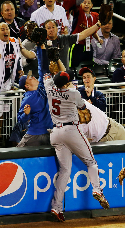 . National League first baseman Freddie Freeman fights with fans for a foul bowl hit by the American League\'s Alexei Ramirez, of the Chicago White Sox, during the seventh inning of the MLB All-Star baseball game, Tuesday, July 15, 2014, in Minneapolis. Freeman did not make the catch. (AP Photo/Paul Sancya)