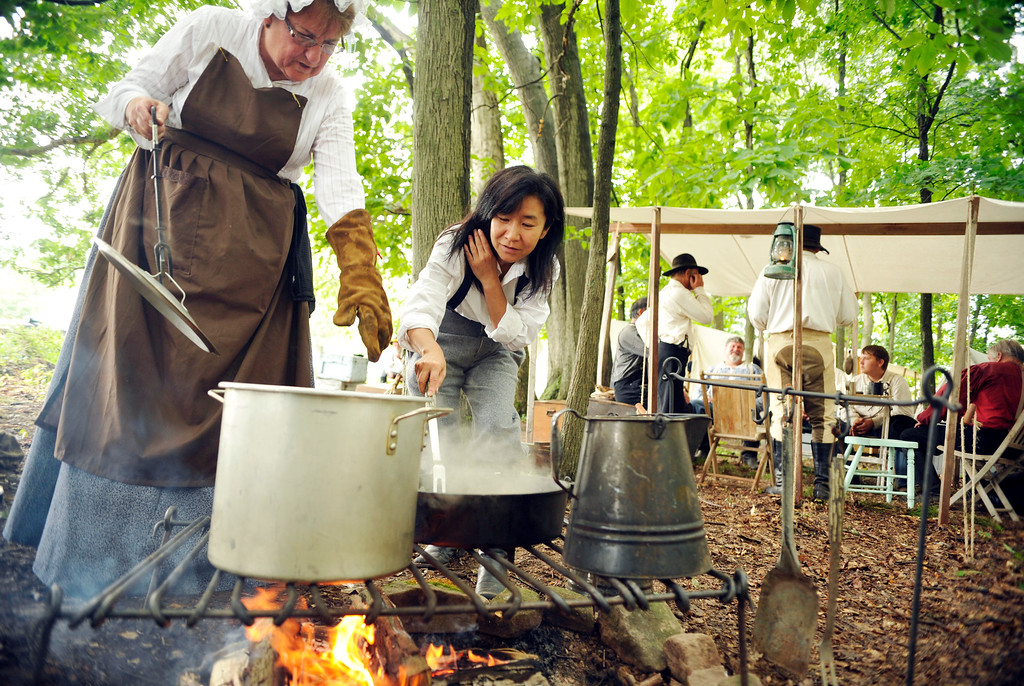 """. Satomi Okada, 52, pulls her hair back as she transfers chicken thighs from a cast iron skillet to a soup pot under the guidance of re-enactor Candy Girard, 62 of Omaha, Neb., at the Blue Gray Alliance\'s re-enactment camp outside Gettysburg, Pa., on Friday, June 28, 2013. Okada, who is from Kobe, Japan, has a three-month tourist visa and is trying to learn what she can about the Civil War, which in Japan is called \""""the North-South War.\"""" A Minnesota friend of hers is re-enacting, and brought her along for the ride. Okada will be a \""""powder monkey\"""" -- assisting with the cannons -- with Terry\'s Texas Rangers Company H during the re-enactments. Some women did go to war -- in cognito -- with their brothers, fathers or husbands during the Civil War, and more than a few female re-enactors today are portraying that by abandoning the hoop skirts and petticoats in favor of men\'s wear and artillery. DAILY RECORD/SUNDAY NEWS - CHRIS DUNN"""