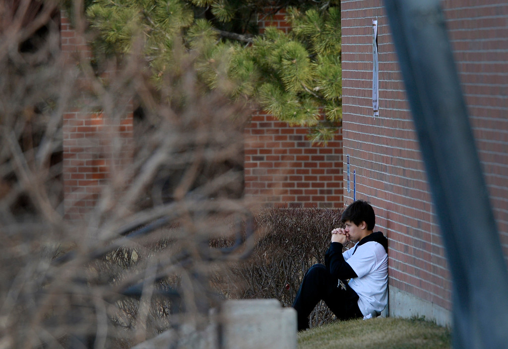 . A student sits outside Arapahoe High School in Centennial, CO December 19, 2013. Seniors and Juniors returned to the school for two hour periods Thursday, Sophomores and Freshmen will return on Friday. (Photo By Craig F. Walker / The Denver Post)