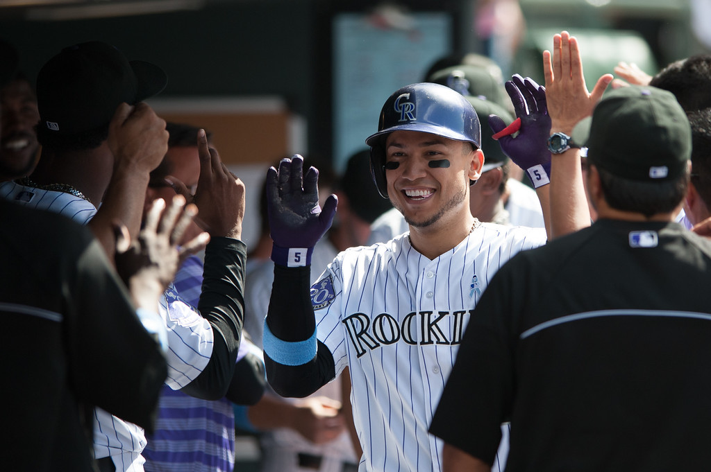 . DENVER, CO - JUNE 16:  Carlos Gonzalez #5 of the Colorado Rockies celebrates a two-run home run with teammates in the dugout during a game against the Philadelphia Phillies at Coors Field on June 16, 2013 in Denver, Colorado. The Rockies beat the Phillies 5-2. (Photo by Dustin Bradford/Getty Images)