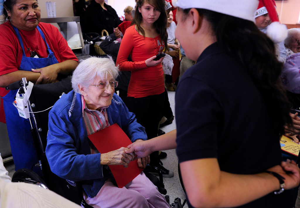 . Sophia Mehos is greeted by students and parents from the Denver Center for International Studies at Ford Elementary School after the kids spend a Saturday singing holiday songs in three different languages to the residents of the Kindred Care nursing home. (Photo by Kathryn Scott Osler/The Denver Post)