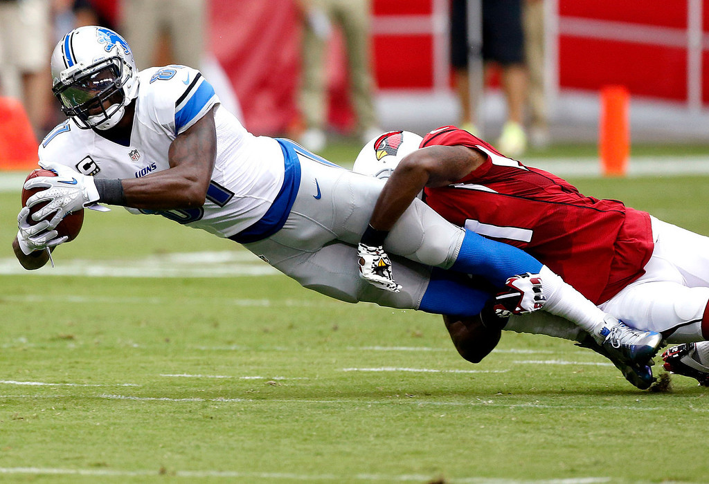 . Detroit Lions wide receiver Calvin Johnson (81) is tackled by Arizona Cardinals cornerback Patrick Peterson during the first half of a NFL football game, Sunday, Sept. 15, 2013, in Glendale, Ariz. (AP Photo/Darryl Webb)