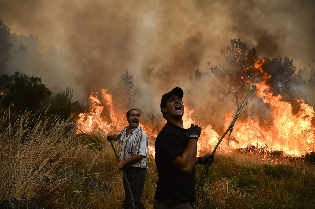 . Locals shout as they try to extinguish a wildfire in Caramulo, central Portugal on August 29, 2013. Five Portuguese mountain villages were evacuated overnight as forest fires intensified in the country\'s north and centre, officials said today. As many as 1,400 firefighters were dispatched Thursday to tackle the blaze in the mountains and another raging further north in the national park of Alvao, where 2,000 hectares (4,900 acres) of pine forest have already been destroyed, according to the local mayor.   PATRICIA DE MELO MOREIRA/AFP/Getty Images