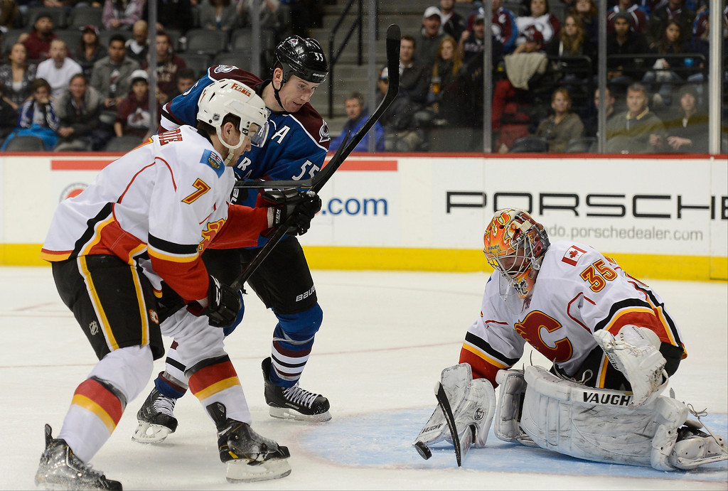 . Joey MacDonald (35) of the Calgary Flames makes the save as Cody McLeod (55) of the Colorado Avalanche and T.J. Brodie (7) of the Calgary Flames look on during the second period April 8, 2013 at Pepsi Center. (Photo By John Leyba/The Denver Post)