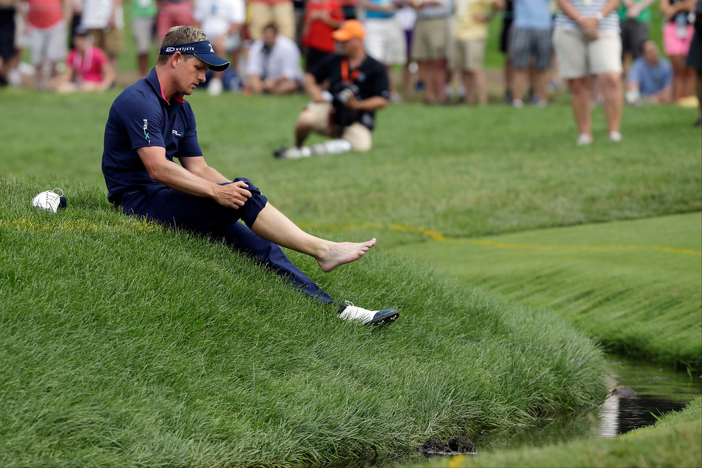 . Luke Donald, of England, pulls up a pant leg to hit from the creek on the fourth hole during the fourth round of the U.S. Open golf tournament at Merion Golf Club, Sunday, June 16, 2013, in Ardmore, Pa. (AP Photo/Morry Gash)