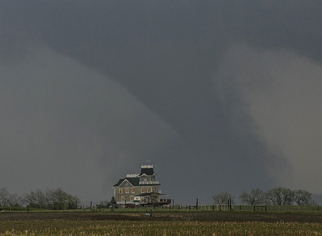 . A tornado forms over a house near  Pilger, Neb., Monday, June 16, 2014. At least one person is dead and at least 16 more are in critical condition after two massive tornadoes swept through northeast Nebraska on Monday. (AP Photo/Mark \'Storm\' Farnik)