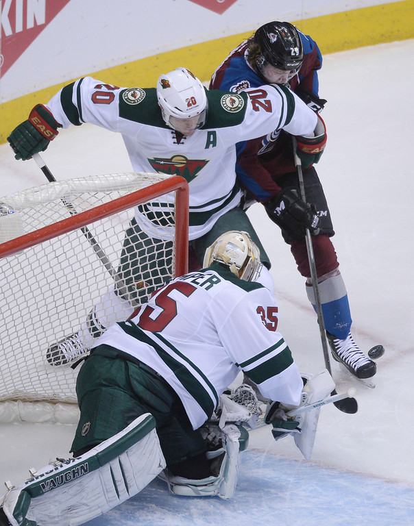 . Nathan MacKinnon (29) of the Colorado Avalanche tries to get a shot off defended by Ryan Suter (20) and Darcy Kuemper (35) of the Minnesota Wild during the first period of action.  (Photo by Karl Gehring/The Denver Post)