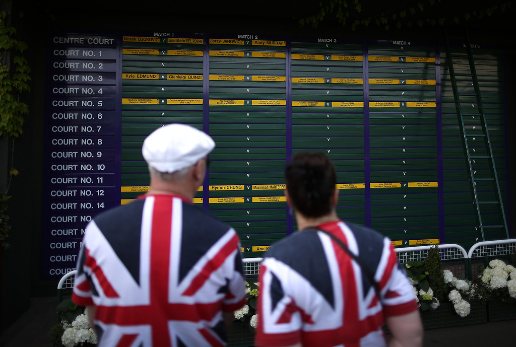 . LONDON, ENGLAND - JULY 05:  Spectators wearing Union flag t-shirts look at a board showing the order of play on day eleven of the Wimbledon Lawn Tennis Championships at the All England Lawn Tennis and Croquet Club on July 5, 2013 in London, England.  (Photo by Peter Macdiarmid/Getty Images)