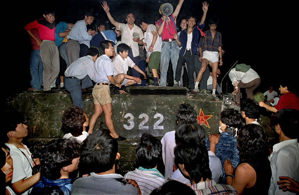 . Civilians hold rocks as they stand on a government armored vehicle near Chang\'an Boulevard in Beijing, early June 4, 1989. Violence escalated between pro-democracy protesters and Chinese troops, leaving hundreds dead overnight. (AP Photo/Jeff Widener)