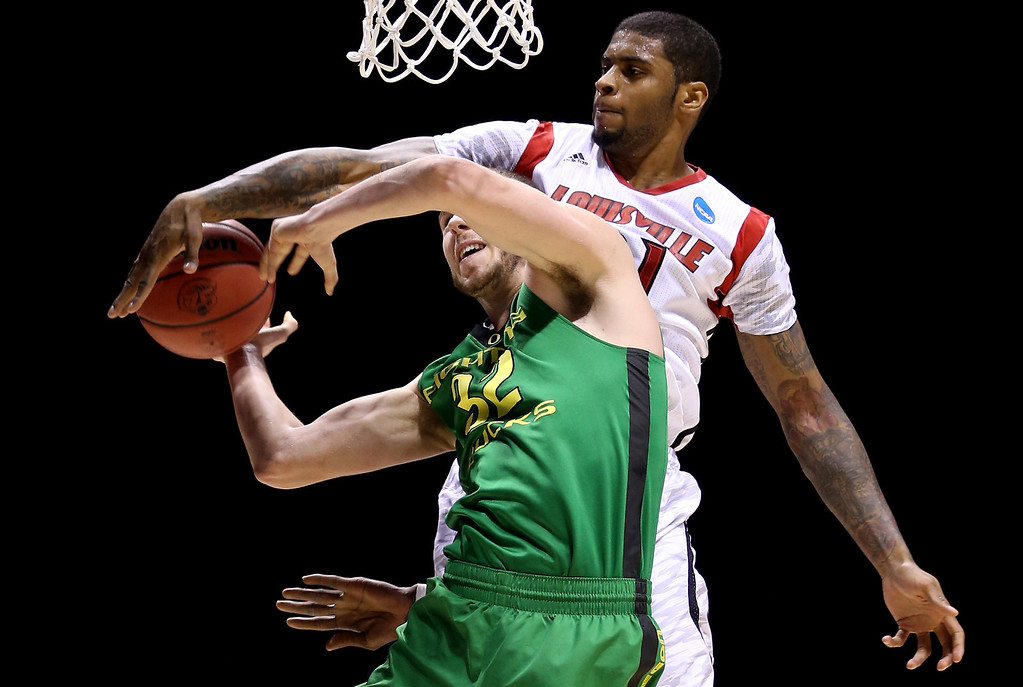 . Chane Behanan #21 of the Louisville Cardinals blocks a shot attempt in the first half against Ben Carter #32 of the Oregon Ducks during the Midwest Region Semifinal round of the 2013 NCAA Men\'s Basketball Tournament at Lucas Oil Stadium on March 29, 2013 in Indianapolis, Indiana.  (Photo by Streeter Lecka/Getty Images)