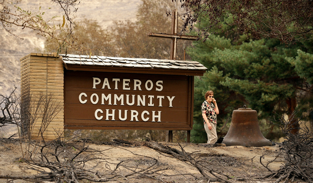 . A woman walks past the sign of a still-standing church after a wildfire the night before destroyed homes surrounding it, Friday, July 18, 2014, in Pateros, Wash. A fire racing through rural north-central Washington destroyed about 100 homes, leaving behind smoldering rubble, solitary brick chimneys and burned-out automobiles as it blackened hundreds of square miles. Friday\'s dawn revealed dramatic devastation, with the Okanagan County town of Pateros, home to 650 people, hit especially hard. (AP Photo/Elaine Thompson)