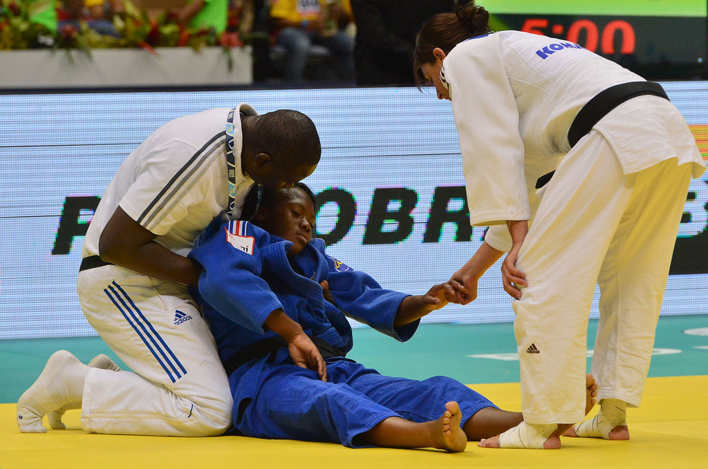 . France\'s Clarisse Agbegnenou (C) is assisted during the women\'s -63kg category final against Israel\'s Yarden Gerbi (out of frame), during the IJF World Judo Championship, in Rio de Janeiro, Brazil, on August 29, 2013.  YASUYOSHI CHIBA/AFP/Getty Images