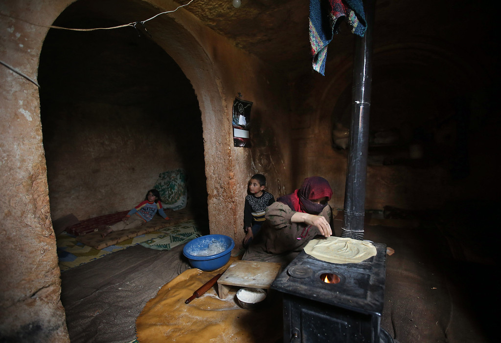 . Nadia, 53, makes bread on a wooden stove, at an underground Roman tomb which she uses as a shelter with her family from Syrian governemnt forces shelling and airstrikes, at Jabal al-Zaweya, in Idlib province, Syria, Thursday, Feb. 28, 2013. Across northern Syria, rebels, soldiers, and civilians are making use of the country\'s wealth of ancient and medieval antiquities to protect themselves from Syria\'s two-year-old war. They are built of thick stone that has already withstood centuries, and are often located in strategic locations overlooking towns and roads. (AP Photo/Hussein Malla)