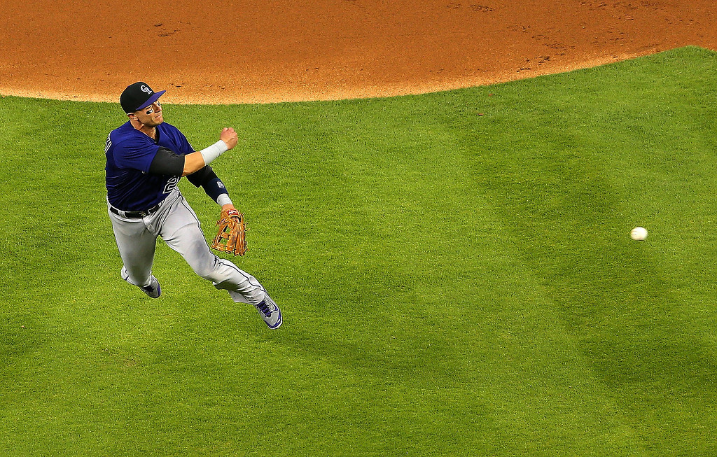 . DJ LeMahieu #9 of the Colorado Rockies makes a throw to first during Opening Day against the Miami Marlins at Marlins Park on March 31, 2014 in Miami, Florida.  (Photo by Mike Ehrmann/Getty Images)