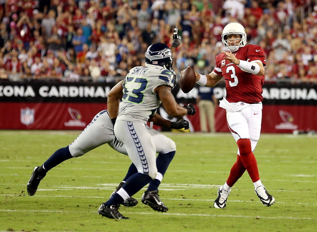 . GLENDALE, AZ - OCTOBER 17: Quarterback Carson Palmer #3 of the Arizona Cardinals scrambles as outside linebacker Malcolm Smith #53 of the Seattle Seahawks defends during a game at the University of Phoenix Stadium on October 17, 2013 in Glendale, Arizona.  (Photo by Christian Petersen/Getty Images)