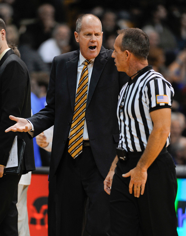 . Colorado University men\'s head basketball coach, Tad Boyle, left, talks with a ref during the game against Kansas  at the Coors Events Center in Boulder Colorado Saturday afternoon, December 07, 2013. (Photo By Andy Cross/The Denver Post)