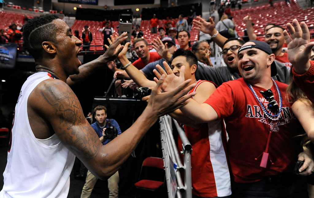 . Arizona forward Rondae Hollis-Jefferson, left, reacts with fans after beating Gonzaga in a third-round game during the NCAA college basketball tournament Sunday, March 23, 2014, in San Diego. Arizona won, 84-61. (AP Photo/Denis Poroy)