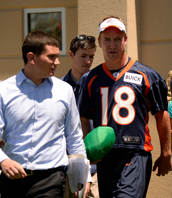 """. Denver Broncos QB Peyton Manning (18) leaves the podium after his press conference carrying a green football after practice May 28, 2014 at Dove Valley. Manning said it was a \""""offensive line business\"""" to be caring it around. (Photo by John Leyba/The Denver Post)"""