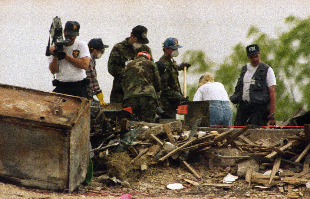 . Investigators search for clues in the rubble of the destroyed Branch Davidian compound near Waco, Texas on Tuesday, April 27, 1993 while another investigator, left, operates a video camera. Lawyers for some of the Branch Davidians questioned the impartiality of an outside team of investigators that concluded the cultists themselves set the fire that destroyed the compound. (AP Photo/Ron Heflin)