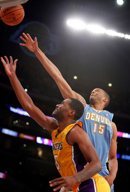 . Los Angeles Lakers forward Shawne Williams, front, shoots with Denver Nuggets forward Anthony Randolph (15) defending in the first quarter during an NBA preseason basketball game Sunday, Oct. 6, 2013 in Los Angeles.  (AP Photo/Alex Gallardo)