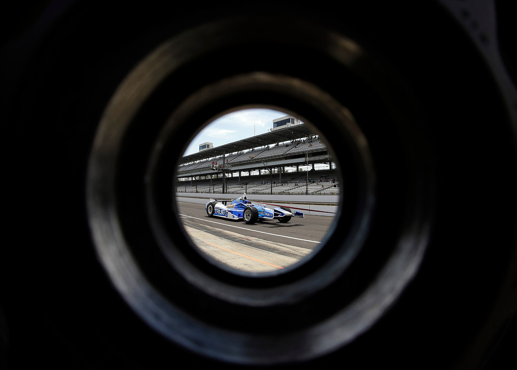 . The car driven by Sebastian Saavedra, of Colombia, is seen through a wheel as its pulled through the pit area during practice for the Indianapolis 500 auto race at the Indianapolis Motor Speedway in Indianapolis, Wednesday, May 15, 2013. (AP Photo/Darron Cummings)