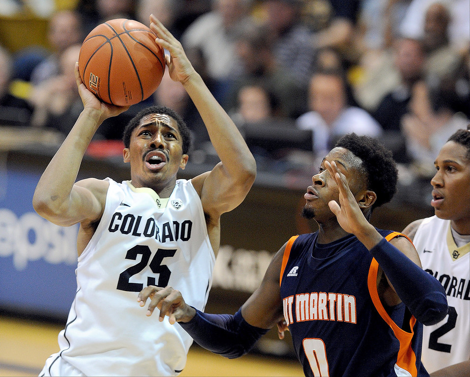 . Spencer Dinwiddie of Colorado, shoots over Tobias Dowdell, of Tenn-Martin, during the second half of the November 10, 2013 game in Boulder, Colorado. (The Daily Camera/Cliff Grassmick)