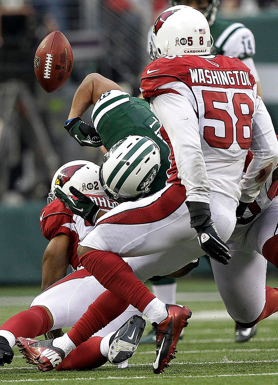 . New York Jets running back Kahlil Bell, center, fumbles a ball as Arizona Cardinals cornerback Greg Toler, bottom, and linebacker Daryl Washington (58) defend on the play during the second half of an NFL football game, Sunday, Dec. 2, 2012, in East Rutherford, N.J. (AP Photo/Kathy Willens)