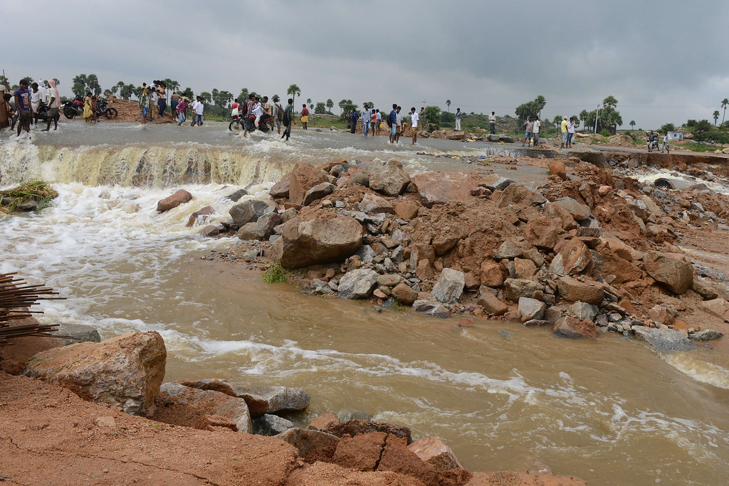 . Indian villagers walk through flood water on a damaged service road following heavy monsoon rain in the Hayat Nagar district, on the outskirts of Hyderabad on October 26, 2013.  Torrential rains made rivers spill their banks in India\'s eastern coastal states of Orissa and Andhra Pradesh, forcing thousands to flee their homes and seek refuge in shelters, two weeks after India\'s most severe cyclone in 14 years lashed the coastline. NOAH SEELAM/AFP/Getty Images
